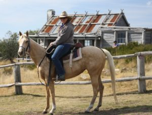 Lady riding palomino horse, standing in front of Hut