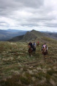 Group of people on horseback riding up steep hill with large mountains in backgroud
