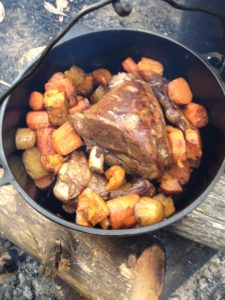 A camp oven filled with a roast and vegetables on a camp fire