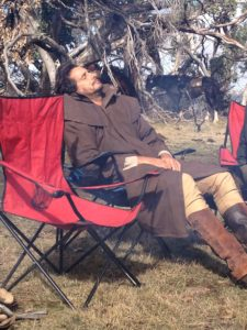 Man asleep in camping chair in sunshine with horses in trees in background