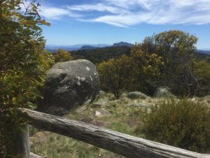 Big rock and tress in foreground with mountains in background