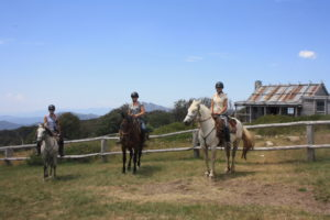 Three people on horseback in front of Hut