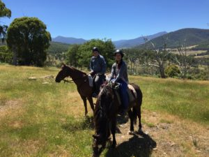 Two people on horseback with Mountain view in background