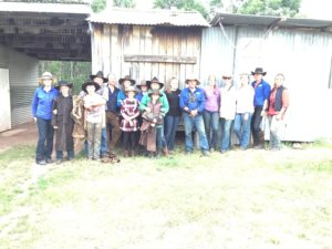 Large group of people standing in front of Hut after finishing a horseride